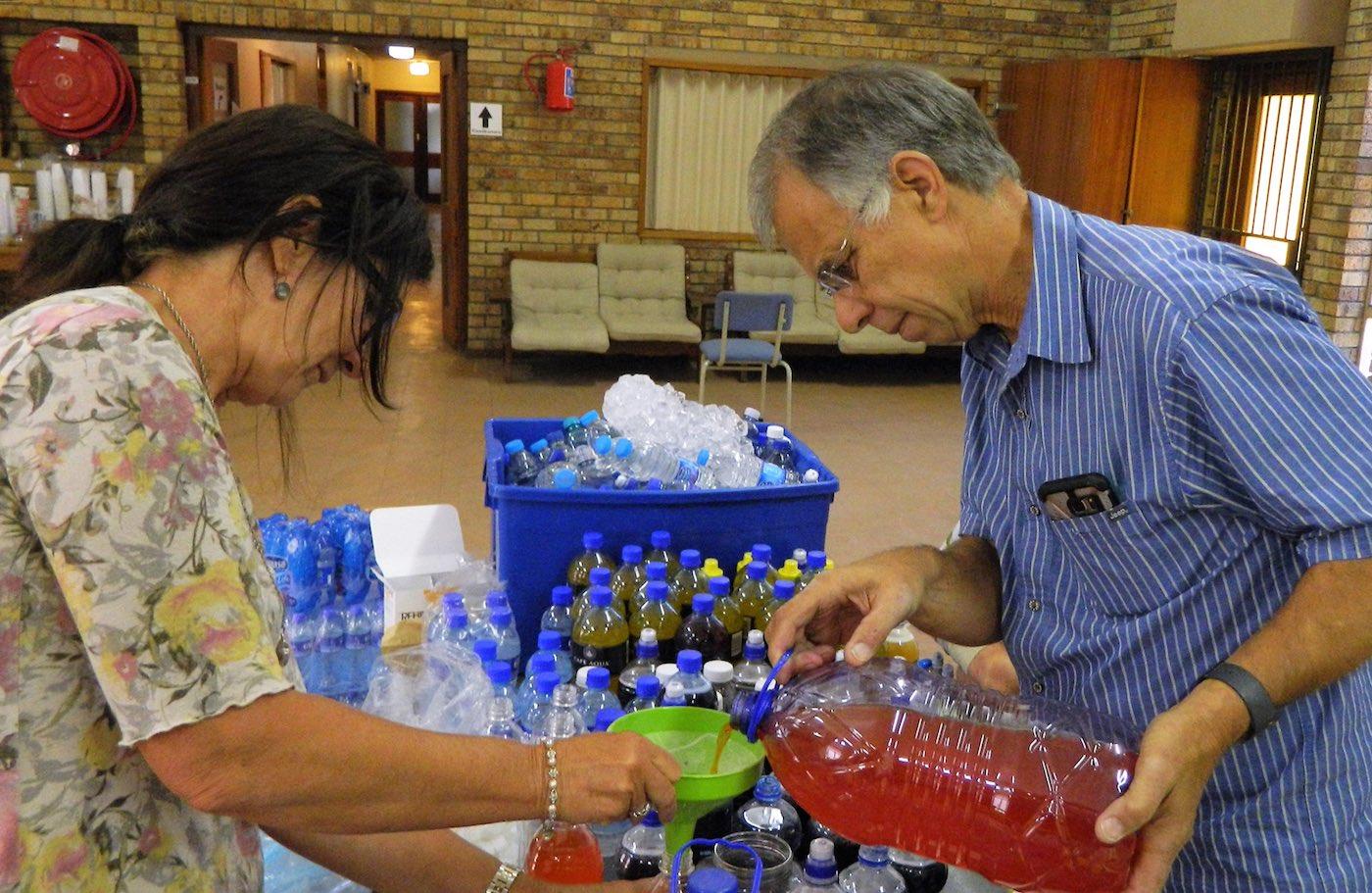 Ds Hennie Fouché van Hottentots-Holland help 'n vrywilliger om energiekoeldrank-stroop te meng en in kleiner houers te skink.
